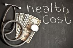 US Currency with health cost written in chalk on wood