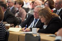 Attendees take notes as speakers share insights for reducing redundancies in care and improving data integration.